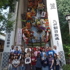 Group photo in front of 'Yamakasa' decoration.